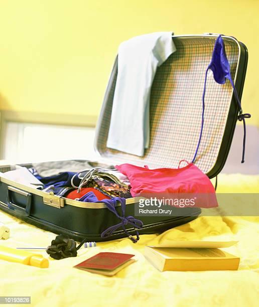 Personal belongings strewn around open suitcase
