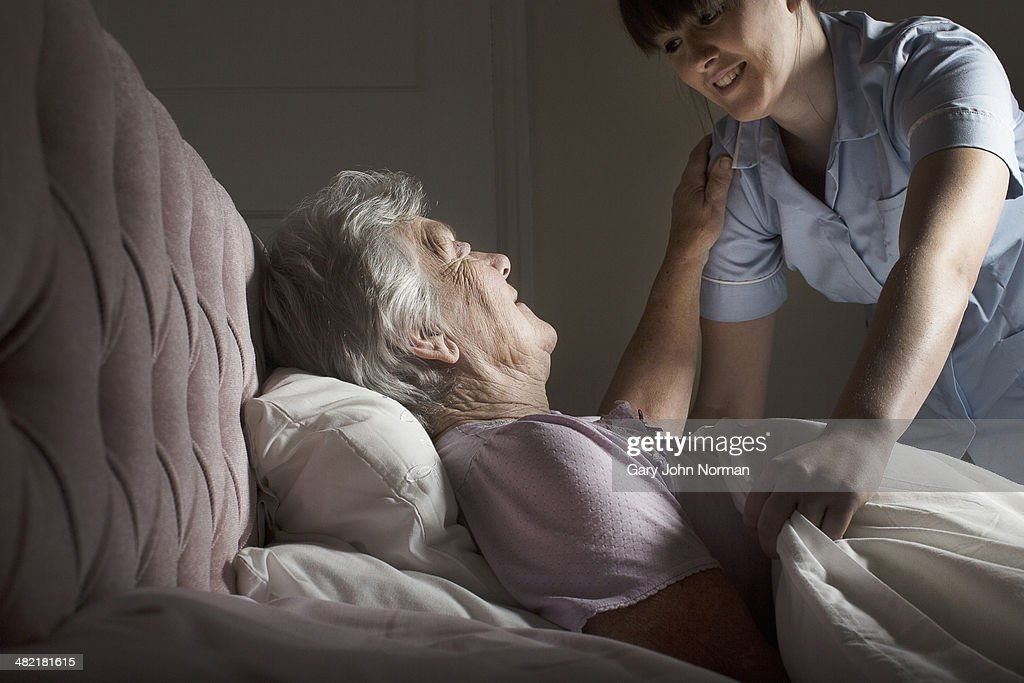 Personal care assistant chatting to senior woman in bed : Stock Photo