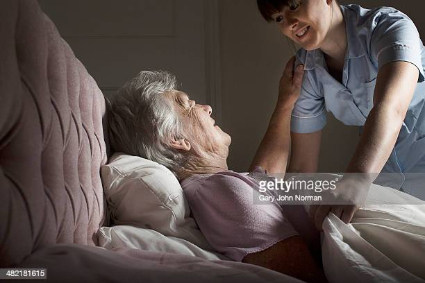 personal care assistant chatting to senior woman in bed - norman elder stock photos and pictures