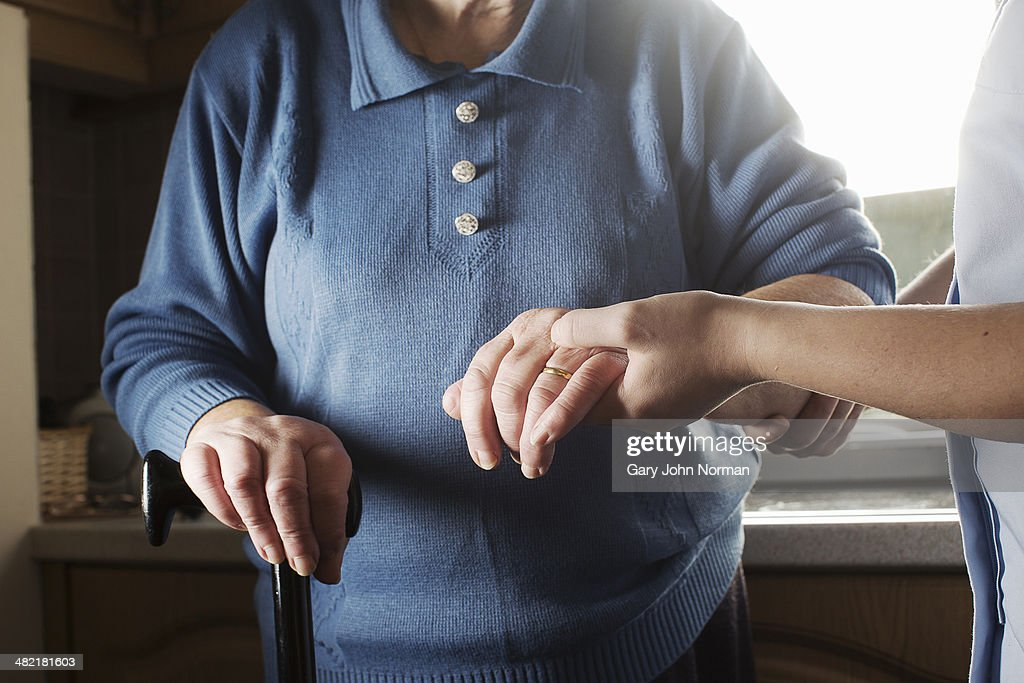Personal care assistant supporting senior woman to walk : Stock Photo