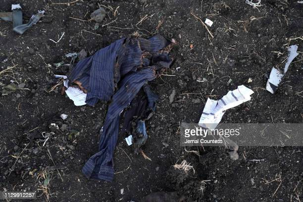 Personal effects lay in the open in the debris field just outside of the impact crater during the continuing recovery efforts at the crash site of...