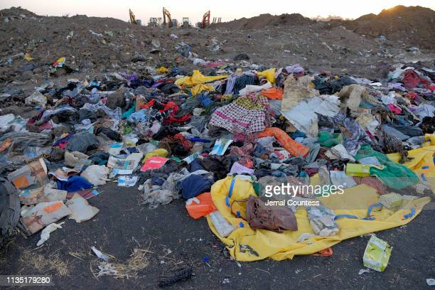 Personal effects lie in a pile just outside of the impact crater after being gathered by workers during the continuing recovery efforts at the crash...