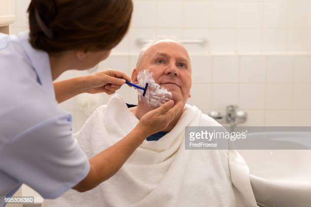 personal hygiene – home caregiver with senior man in bathroom - body care stock pictures, royalty-free photos & images
