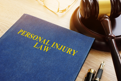 Personal injury law on a desk and gavel. 996348474