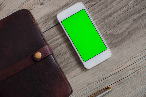 Personal organizer and mobile device with green screen on a wooden table - gettyimageskorea