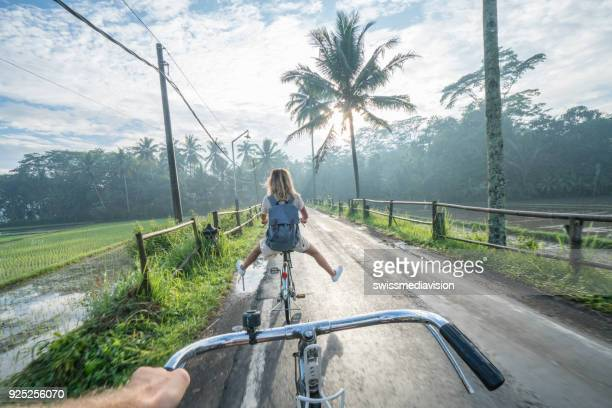 Personal perspective- couple cycling near rice fields at sunrise, Indonesia
