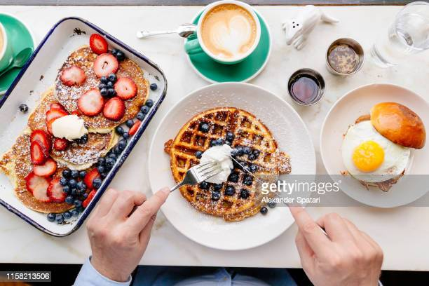 personal perspective directly above view of man eating breakfast at a cafe - syrup stock pictures, royalty-free photos & images