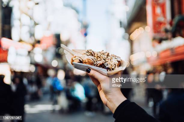 personal perspective of a female traveller holding freshly made traditional japanese street-style snack takoyaki (octopus balls) against downtown city street while visiting osaka - travel ストックフォトと画像