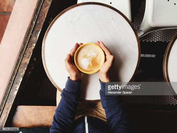 personal perspective of a man holding cappuccino bowl with two hands - taken on mobile device stock photos and pictures
