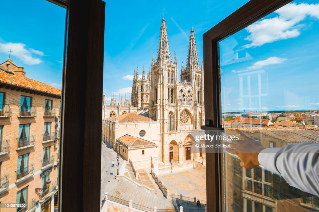 Personal perspective of a man opening window and looking at Burgos cathedral, Spain : Stock Photo