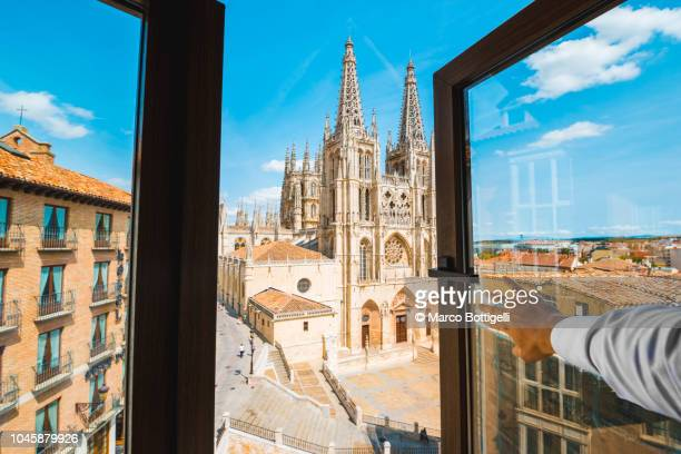 Personal perspective of a man opening window and looking at Burgos cathedral, Spain