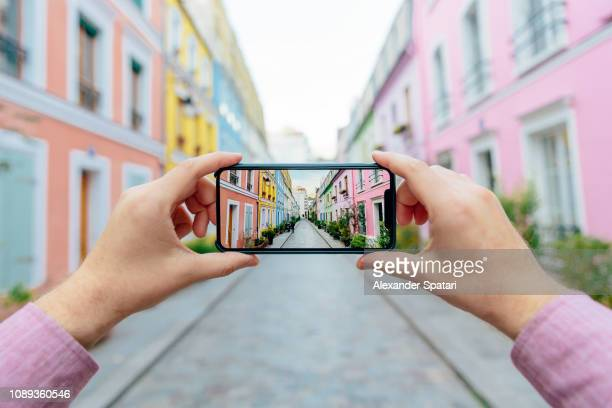 personal perspective of a man photographing colorful street rue cremieux with smartphone, paris, france - influencer stock pictures, royalty-free photos & images