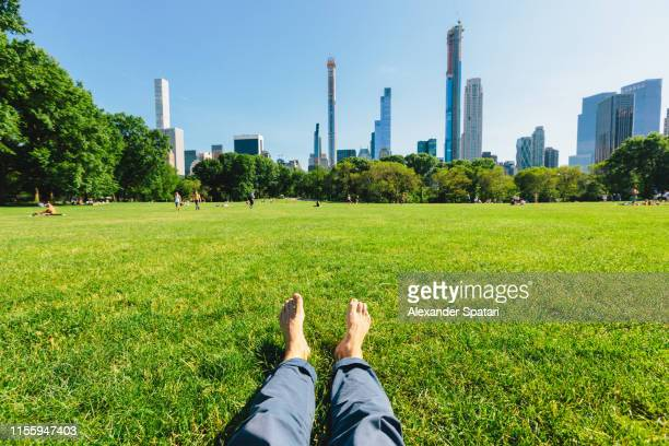 personal perspective of a man relaxing barefoot in central park, new york city - personal perspective stock pictures, royalty-free photos & images