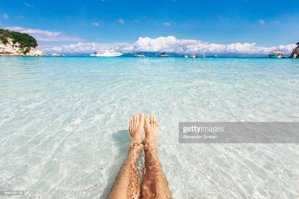 Personal perspective of a man swimming in the clear turquoise sea : Stock Photo