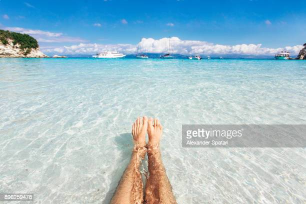 Personal perspective of a man swimming in the clear turquoise sea