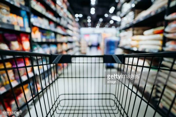 personal perspective of a shopper pushing shopping trolley along product aisle while shopping in a supermarket - mercado espaço de venda no varejo - fotografias e filmes do acervo