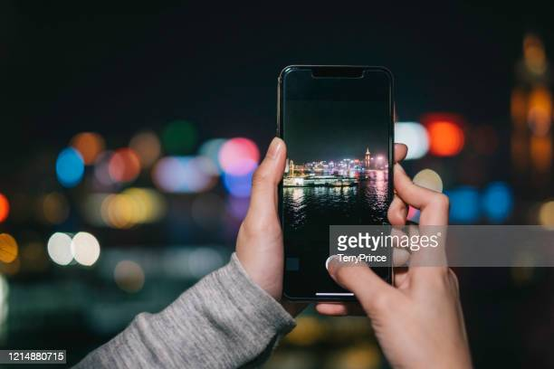 personal perspective of a young female photographing a colorful night scene in victoria harbour of hong kong using her mobile phone. - launch event stock pictures, royalty-free photos & images