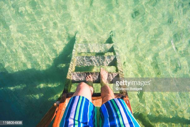 personal perspective of barefoot man going down steps into the caribbean sea - personal perspective stock pictures, royalty-free photos & images