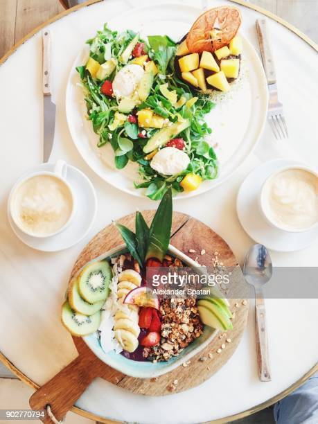 Personal perspective of brunch with smoothie bowl and healthy fresh salad with mango