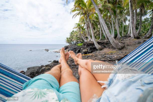 personal perspective of couple relaxing on hammock, feet view - big island hawaii islands stock pictures, royalty-free photos & images