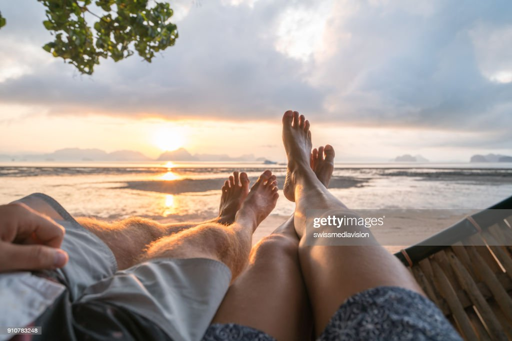 Personal perspective of couple relaxing on hammock, feet view : Stock Photo
