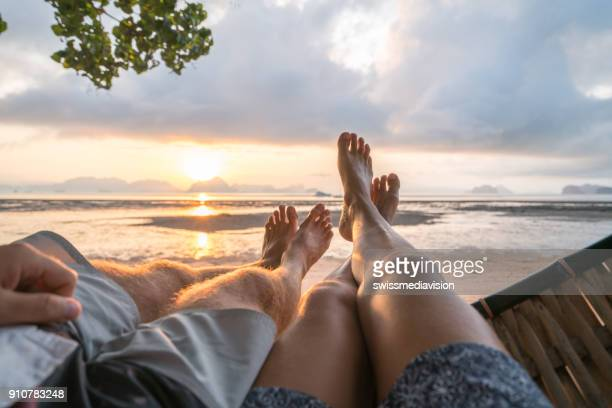 Personal perspective of couple relaxing on hammock, feet view