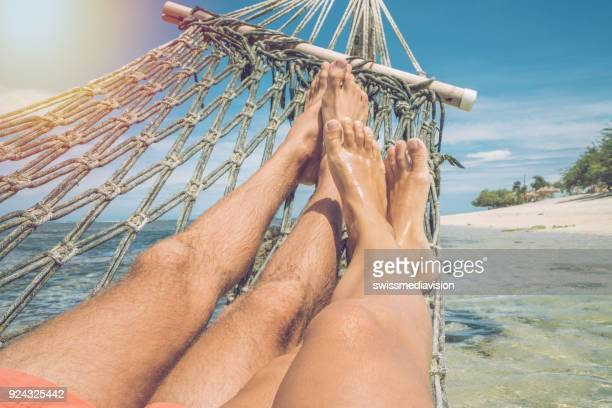 Personal perspective of couple relaxing on hammock over the sea, feet view