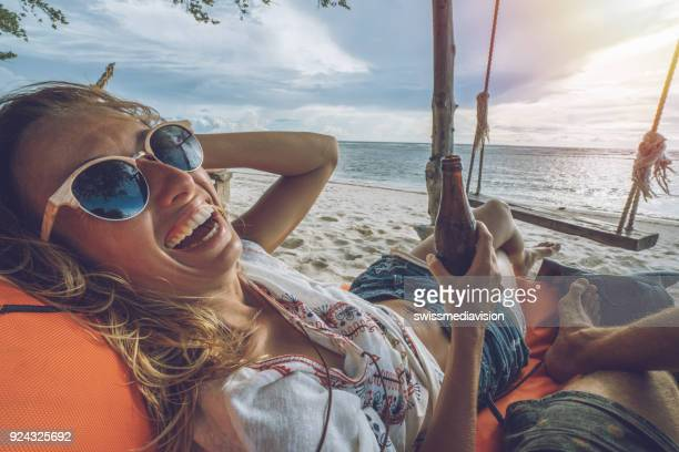 personal perspective of couple relaxing on the beach at sunset bar - indonesia photos stock photos and pictures
