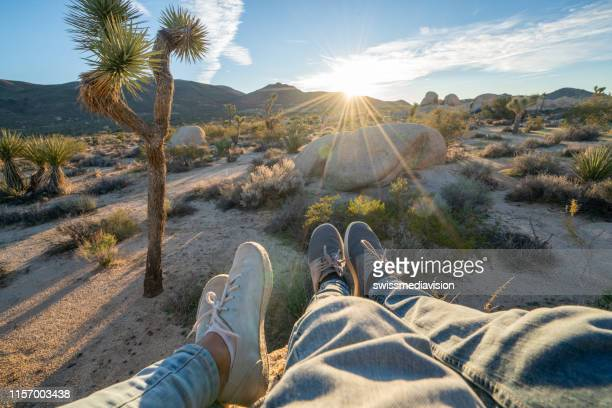 personal perspective of couple relaxing on top of boulder rock at sunrise; feet view;  people travel vacations relaxation concept - joshua stock pictures, royalty-free photos & images
