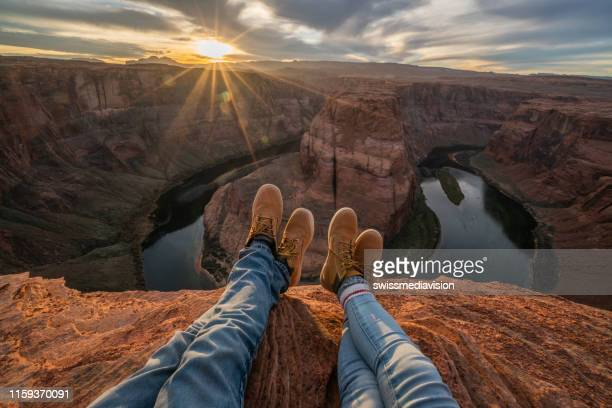 personal perspective of couple relaxing on top of grand canyon; feet view;  people travel vacations relaxation concept - arizona stock pictures, royalty-free photos & images