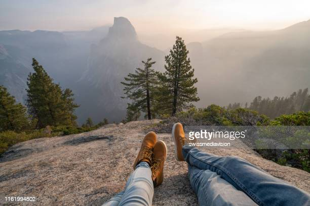 personal perspective of couple relaxing on top of yosemite valley; feet view - yosemite valley stock photos and pictures