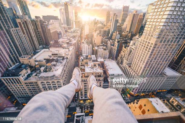 personal perspective of feet hanging down from a ledge over new york city at sunset - at the edge of stock pictures, royalty-free photos & images