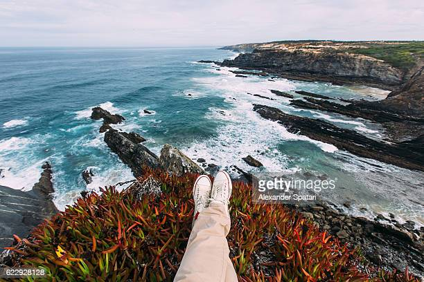 Personal perspective of feet in white canvas shoes with the view towards ocean and cliffs, high angle view