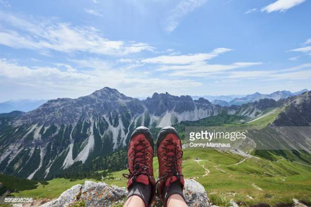 Personal perspective of female hikers hiking boots over valley in Tannheim mountains, Tyrol, Austria