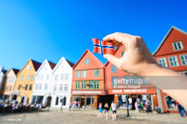 personal perspective of hand holding a norwegian flag souvenir in bergen, norway - norwegian flag stock pictures, royalty-free photos & images