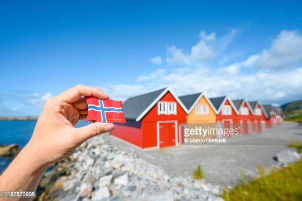 personal perspective of hand holding a norwegian flag souvenir against colorful rorbuer in alnes, norway - norwegian flag stock pictures, royalty-free photos & images