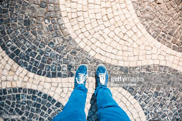 personal perspective of human feet standing on a tiled floor in lisbon, portugal. - blue shoe stock pictures, royalty-free photos & images