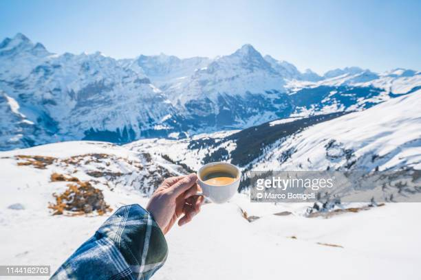 personal perspective of human hand holding a cup of coffee in the swiss alps - standpunt stockfoto's en -beelden