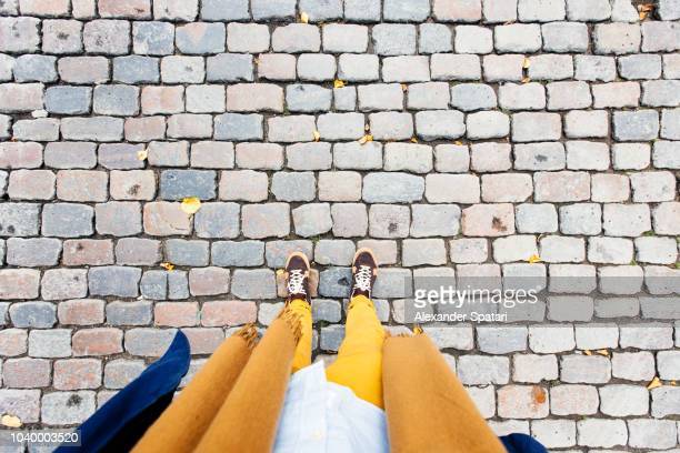 personal perspective of low section of a man in sneakers and yellow trousers at cobblestone street - cobblestone stock pictures, royalty-free photos & images