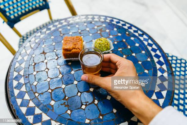 personal perspective of man drinking sweet tea with morrocan pastries at cafe - île de france stock-fotos und bilder