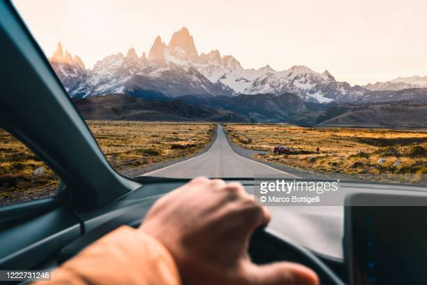 personal perspective of man driving a car in patagonia, argentina - lateinamerika stock-fotos und bilder