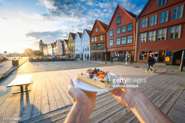 personal perspective of man holding a norwegian waffle in bergen, norway - cultura norvegese foto e immagini stock