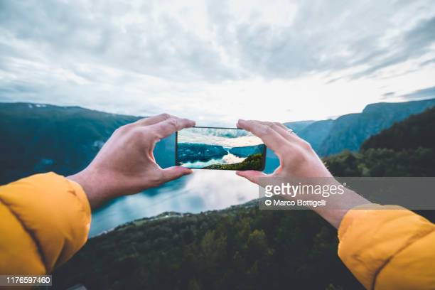 personal perspective of man photographing a norwegian fjord with smartphone, norway - fotohandy stock-fotos und bilder