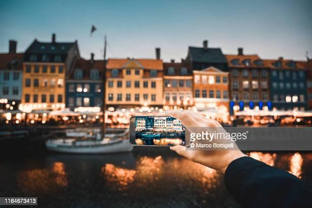 personal perspective of man photographing nyhavn waterfront, copenhagen - モバイル撮影 ストックフォトと画像