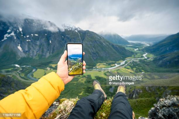 personal perspective of man photographing romsdalen valley, norway - photo messaging stock photos and pictures