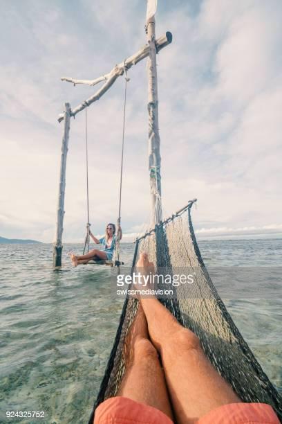 perspectiva personal de hombre relajarse en la hamaca sobre el mar, mujer en columpio - lombok fotografías e imágenes de stock