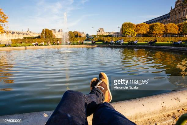 personal perspective of man resting by the fountain in tuileries garden, paris, france - fountain stock pictures, royalty-free photos & images