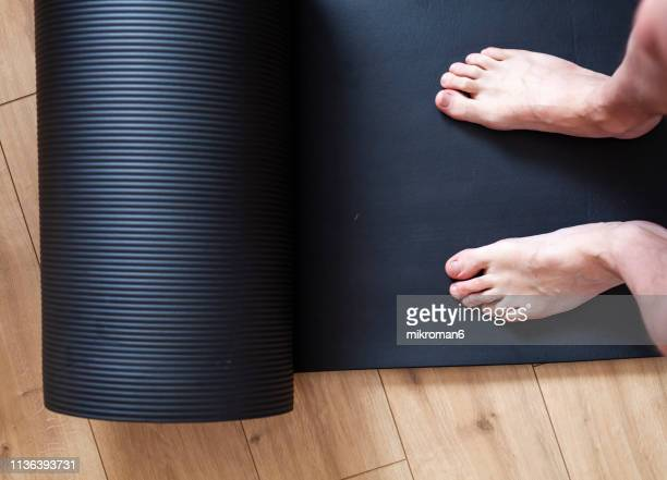 Personal perspective of man standing on exercise mat