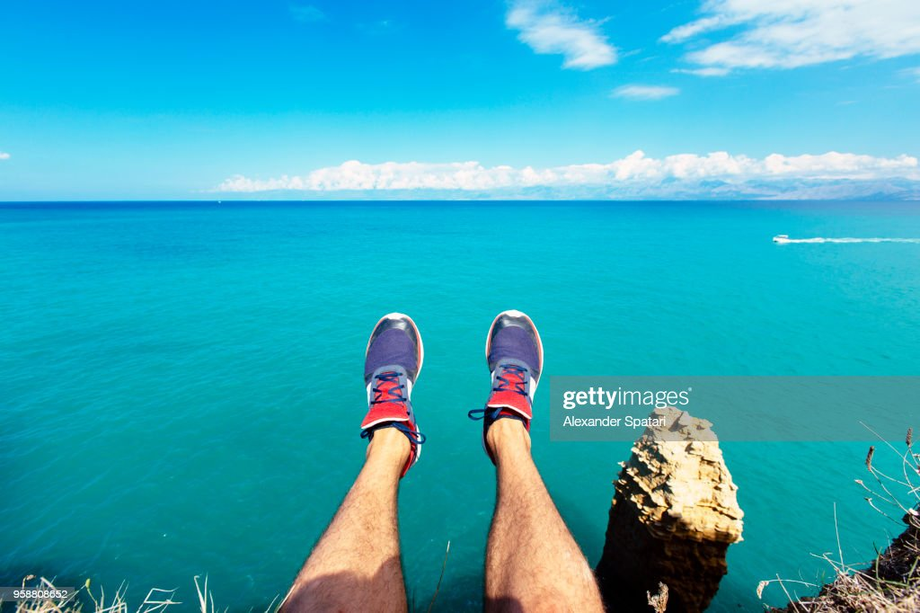 Personal perspective of man's feet against blue sea and sky : Stock Photo