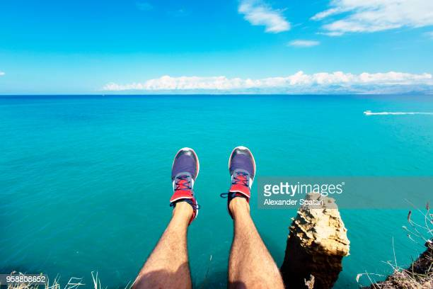 Personal perspective of man's feet against blue sea and sky